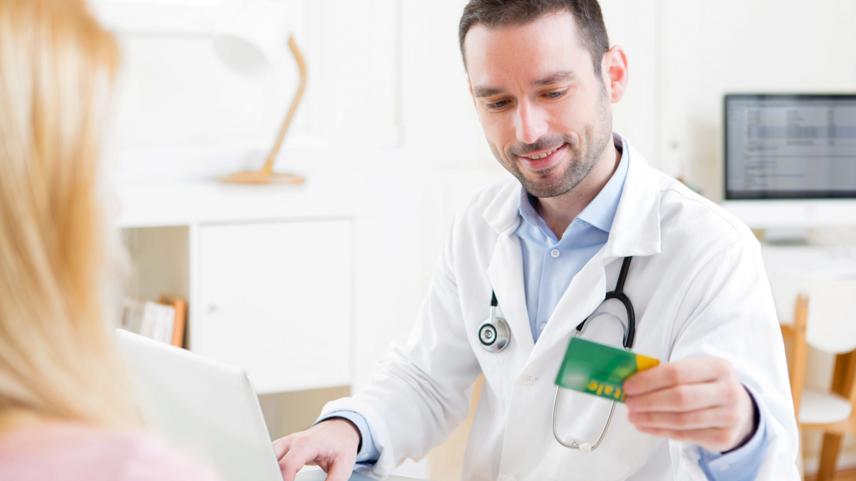 View of a Young attractive doctor taking health insurance card to patient