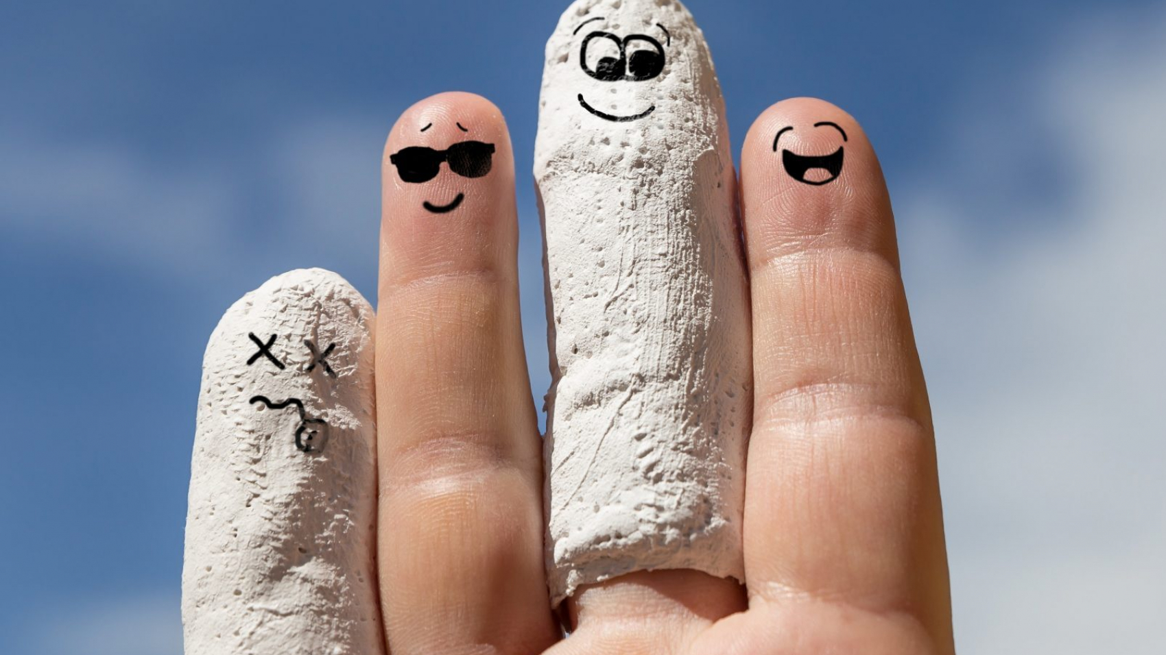 Hand vor blauem Himmel, eingegipste Finger, Konzept arbeitsunfähig oder Unfallversicherung
