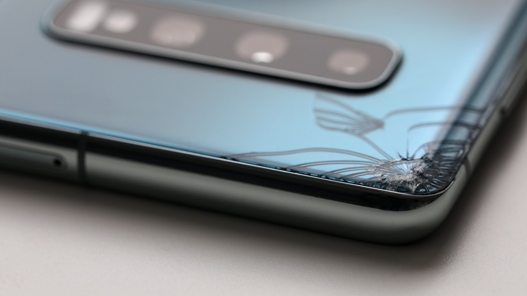 modern-smartphone-lying-table-with-crack-corner-close-up